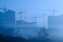 Guindastes sobre construções novas na manhã nevoenta adiantada Fotografia de Stock Royalty Free