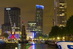 Guindastes velhos iluminados e prédios de escritórios modernos na noite no porto histórico de Rotterdam Imagens de Stock