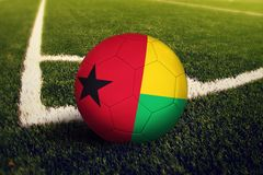 Guinea Bissau ball on corner kick position, soccer field background. National football theme on green grass.  royalty free stock photography