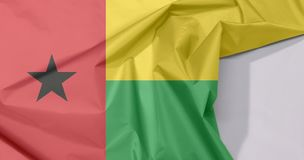 Guinea Bissau fabric flag crepe and crease with white space. Guinea Bissau fabric flag crepe and crease with white space, vertical red line with black star two royalty free stock photo