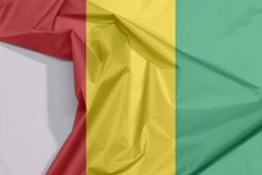 Guinea Bissau fabric flag crepe and crease with white space. Guinea Bissau fabric flag crepe and crease with white space, vertical red line with black star two stock image