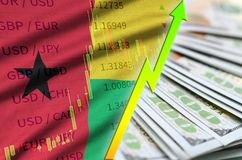 Guinea Bissau flag and chart growing US dollar position with a fan of dollar bills. Concept of increasing value of US dollar currency royalty free stock photos
