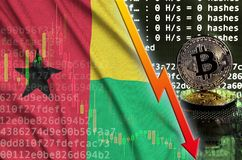 Guinea Bissau flag and falling red arrow on bitcoin mining screen and two physical golden bitcoins. Concept of low conversion in cryptocurrency mining stock images