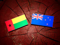 Guinea Bissau flag with New Zealand flag on a tree stump isolate. D royalty free stock photography