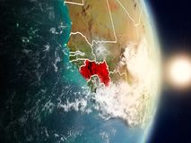 Guinea during sunrise. Highlighted in red on planet Earth with visible country borders. 3D illustration. Elements of this image furnished by NASA Stock Image