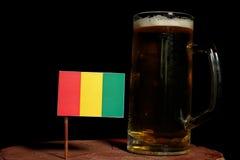 Guinean flaga z piwnym kubkiem na czerni Obraz Stock