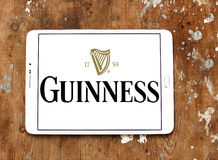 Guinness beer logo. Logo of beer drinks company guinness on samsung tablet on wooden background Royalty Free Stock Image