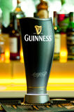 Guinness Beer Tap. A portrait of Guinness beer tap with bottles of spirit at the blurred background. Photo was taken on 13 April 2011 royalty free stock image