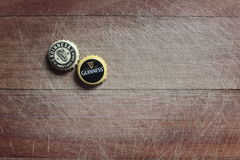 Guinness bottle caps. On a wood background Stock Photo