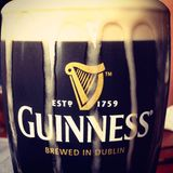 Guinness draught. A tasty pint of Guinness draft beer with the head overflowing royalty free stock photos