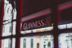 Guinness logo on pub`s awnings shot from inside the window. DUBLIN, IRELAND - 28th March, 2018: Guinness logo on pub`s awnings shot from inside the window Stock Photo