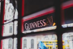 Guinness logo on pub`s awnings shot from inside the window. DUBLIN, IRELAND - 28th March, 2018: Guinness logo on pub`s awnings shot from inside the window Stock Images