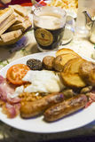Guinness. Mug filled with Guinness and traditional breakfast in an Ireland pub onion egg potato sausage bread meatballs meatball pea stock images