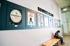 Guinness Storehouse in Dublin. Tourist resting during a guide tour in Guinness Storehouse in Dublin. Old advertising Guinness banners Royalty Free Stock Photo
