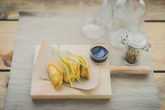 Guiozas giapponesi con la salsa di soia sulla tavola di spezzettamento di legno immagine stock libera da diritti