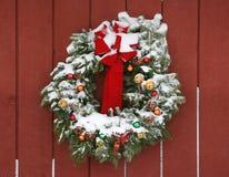 Guirlande avec la neige sur la grange photographie stock libre de droits