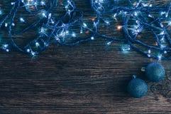 Guirlande avec les lumières et les boules bleues de Noël sur un vieux fond en bois Fond de fête Photo stock