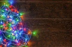 Guirlande brûlante de LED sur un fond en bois foncé Préparation pour Photo stock