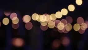Guirlande brouillée de lumières de nuit dans le bokeh Noël et fond Defocused banque de vidéos