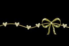 Guirlande d'or avec l'arc de cadeau et les coeurs brillants Photos stock