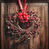 Guirlande de Noël avec le ruban rouge et baies sur en bois Photographie stock libre de droits