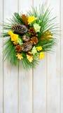 Guirlande de Noël avec les roses jaunes de tissu et les pinecones d'or Images libres de droits