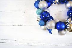Guirlande de Noël des boules bleues et blanches sur la surface blanche en bois Photographie stock libre de droits