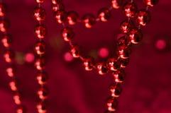 Guirlande de Noël faite à partir de petites perles rouges Sur un fond rouge Images stock