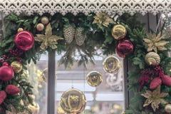 Guirlande de Noël, un plan rapproché de guirlande autour d'une fenêtre avec les décorations brillantes, boules, cônes, baies, fon image libre de droits