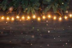 Guirlande de scintillement de Noël avec des branches d'arbre et de cônes de sapin sur le fond en bois Configuration plate image stock