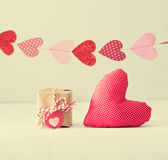 Guirlande des coeurs au-dessus du petit giftbox et du coussin rouge de coeur Images libres de droits