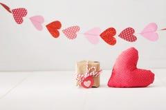 Guirlande des coeurs au-dessus du petit giftbox et du coussin rouge de coeur Photo stock