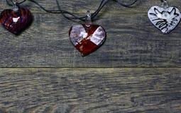 Guirlande des coeurs en verre sur le vieux fond en bois foncé Photo stock