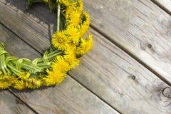 Guirlande des fleurs jaunes - pissenlits sur un fond en bois Image stock