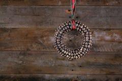 Guirlande et ruban de Noël de cône de pin de forme ronde sur vieux rustique Images stock