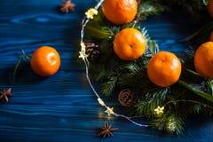 Guirlande faite à partir des mandarines fraîches avec des feuilles et des branches impeccables avec des cônes sur la table en boi photos stock