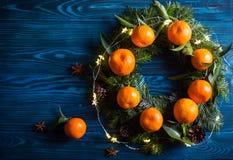 Guirlande faite à partir des mandarines fraîches avec des feuilles et des branches impeccables avec des cônes sur la table en boi image stock
