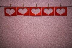 Guirlande rouge de forme de coeur sur le fond rose Photographie stock libre de droits