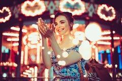 Guirlandes de sourire et parlantes de belle jeune femme des lumières à la ville Images stock