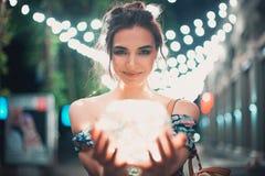 Guirlandes de sourire et parlantes de belle jeune femme des lumières à la ville Photographie stock