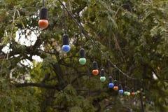 Guirlandes des lampes de couleur accrochant sur la terrasse d'été Photographie stock libre de droits