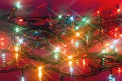 Guirlandes multicolores rougeoyantes de Noël reflétées Images stock