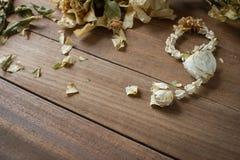 Guirlandes sèches de fleur avec les feuilles sèches sur le plancher en bois Photographie stock libre de droits