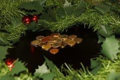 Guirnalda artificial del Año Nuevo con las bolas y el montón rojos de monedas euro en el centro fotografía de archivo libre de regalías