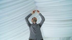 Guirnalda blanca colgante de las linternas del hombre al techo almacen de metraje de vídeo