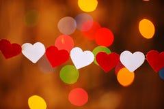 Guirnalda con los corazones rojos y blancos en boke Fotos de archivo