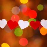 Guirnalda con los corazones rojos y blancos en boke Fotografía de archivo