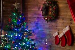 Guirnalda de la decoración cerca del árbol de navidad con las luces Foto de archivo