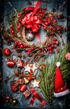 Guirnalda de la Navidad con las decoraciones rojas del día de fiesta y sombrero de Papá Noel en fondo de madera rústico azul imagen de archivo