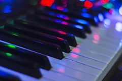 Guirnalda de la Navidad con las luces en un piano electrónico - decoración para la celebración de la Navidad y del Año Nuevo Foto de archivo libre de regalías